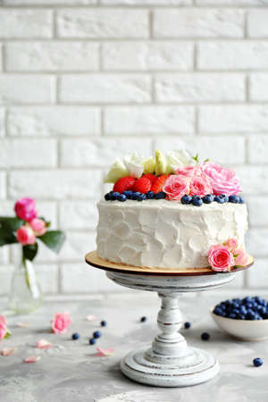 Delicious cake decorated with berries and flowers on brick wall background