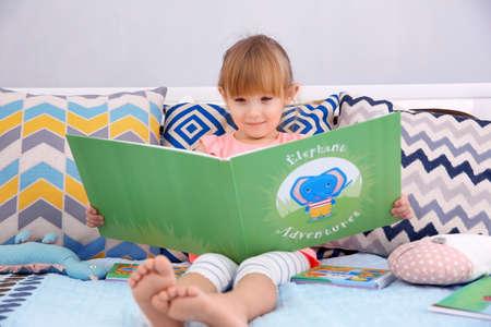 Mała śliczna dziewczyna czytająca książkę