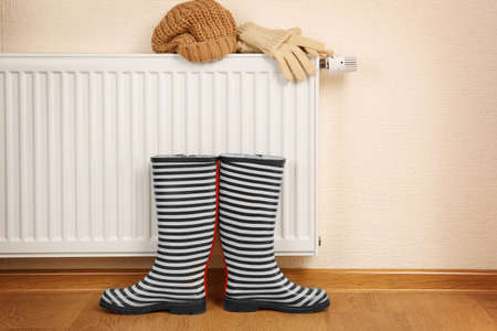 Heating radiator with rubber boots and warm clothes indoor