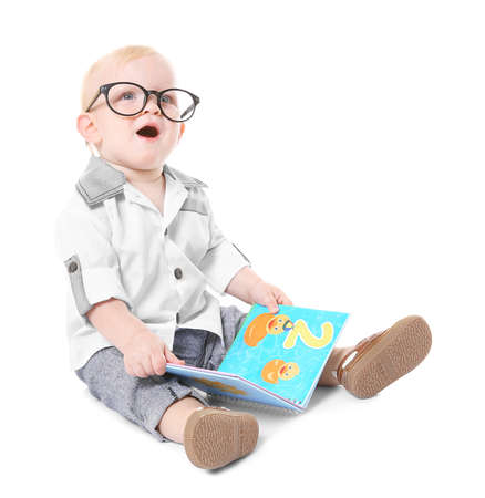 Baby boy with book sitting on white background