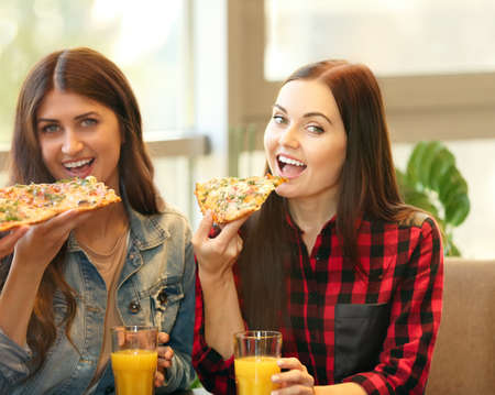 Cheerful young women eating tasty pizza in cafe