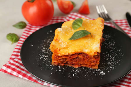 Black plate with delicious lasagna and napkin on table