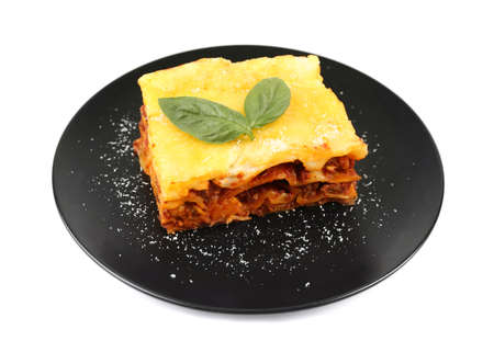 Black plate with delicious lasagna on white background