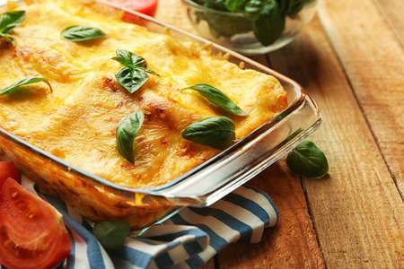 Traditional lasagna in glass baking dish and tomatoes on wooden table Standard-Bild