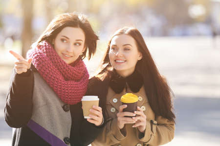 Cheerful young women drinking coffee outdoors Stock Photo