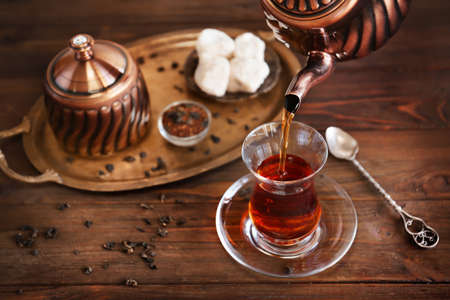 Poring Turkish tea into traditional glass on wooden table closeup