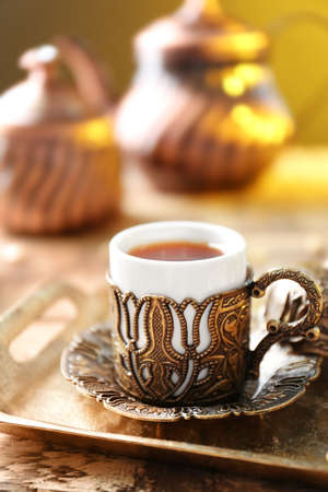 Turkish tea in cup with holder on metal tray closeup
