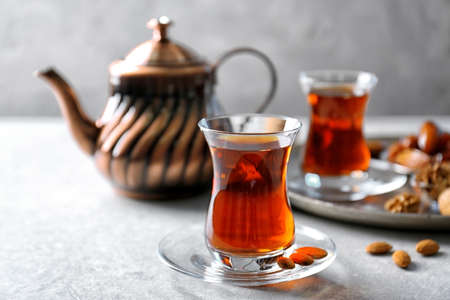 Turkish tea in traditional glass with nuts on table closeup