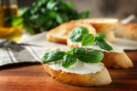 Delicious bruschetta with cream cheese and basil on wooden table, closeup