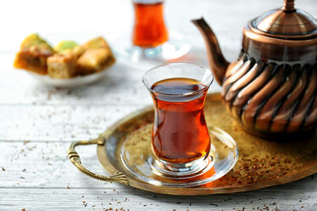 Turkish tea in traditional glass and metal teapot on wooden table closeup