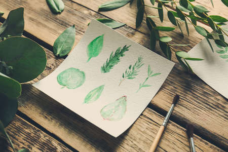 Watercolor painting with leaves on wooden table