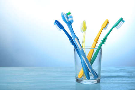 Toothbrushes in glass on color background