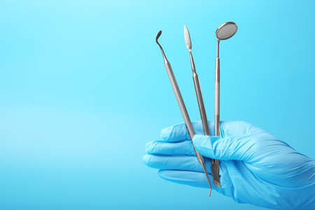 Hand holding dental equipment on blue background Stock Photo