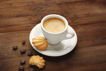 Cup of tasty coffee with cookies and beans on wooden table Imagens