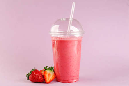 Delicious strawberry milkshake in plastic cup on pink background