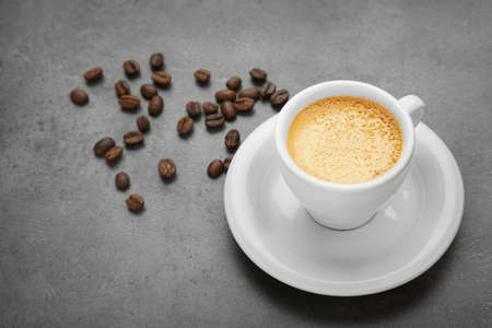 Cup of coffee and beans on grey table