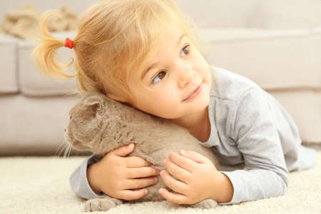 Adorable little girl with cute cat lying on the floor at home