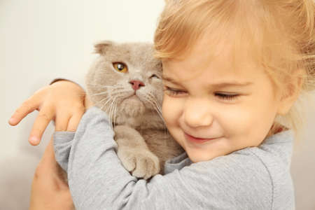 Closeup of adorable little girl embracing cute cat in the room