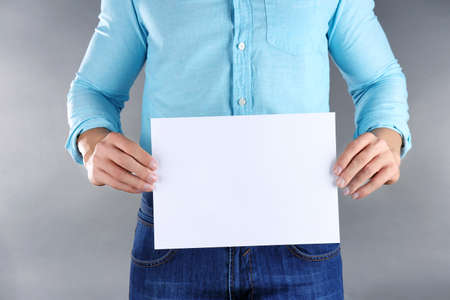 Man holding sheet of paper with space for text on grey background