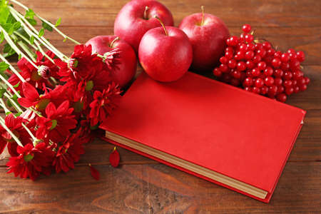Red book with apples, viburnum berries and flowers on wooden table