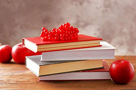 Pile of books and viburnum berries on wooden table Stock Photo