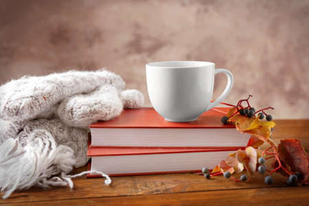 Books with cup of tea, scarf and autumn leaves on wooden table
