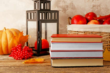 Autumn composition with pile of books on wooden table