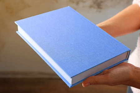 Female hands holding book in blue cover on grey background 版權商用圖片