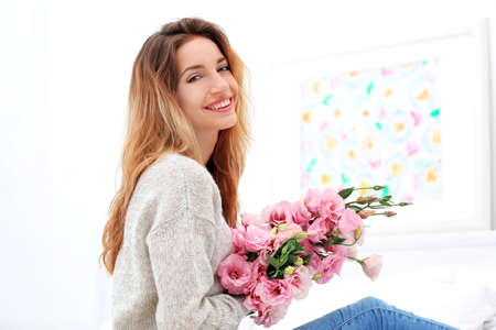 Happy young woman with beautiful bouquet of eustoma flowers sitting on bed at home Stok Fotoğraf