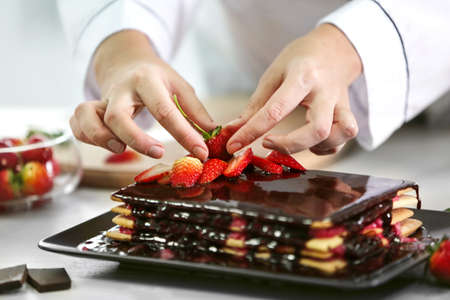 Cooking concept. Professional confectioner decorating delicious cake with strawberry, closeup