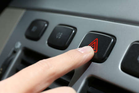 Male hand pressing emergency warning button on car console, closeup