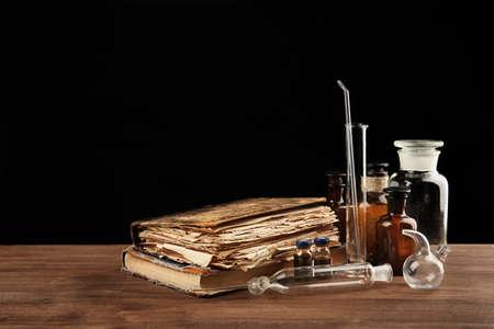Vintage medicine bottles and books on wooden table Reklamní fotografie