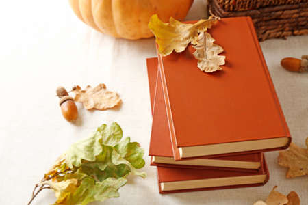 Closeup of books and autumn leaves on the table