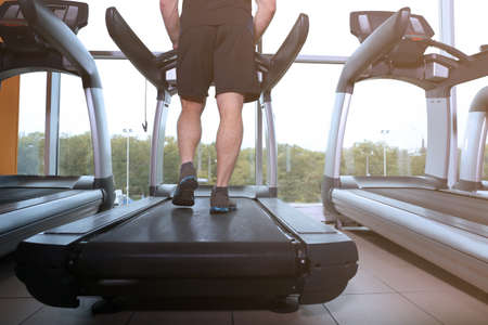 Young handsome man running on treadmill in gym