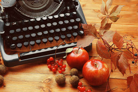 Autumn composition with old typewriter on wooden background Stock Photo