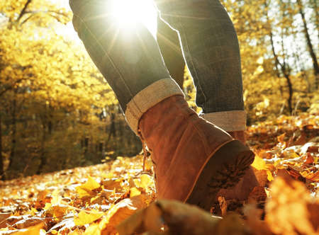 Legs of woman walking in autumn park on sunny day