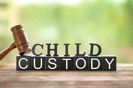 Text CHILD CUSTODY made of black blocks and letters with judge gavel on table against blurred background, closeup