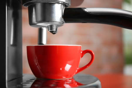 New electric coffee maker with red cup, close up