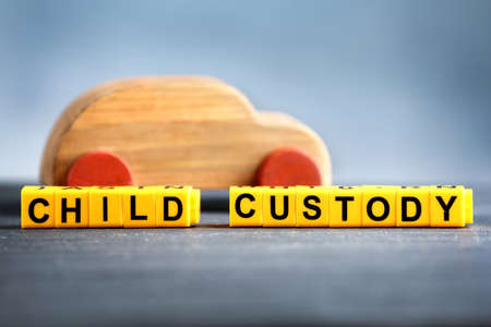 Text CHILD CUSTODY made of yellow blocks with wooden car on table against blurred background, closeup
