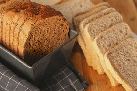 Sliced rye bread on wooden table closeup