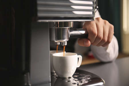 Male barista making fresh espresso in coffee maker, close up Imagens