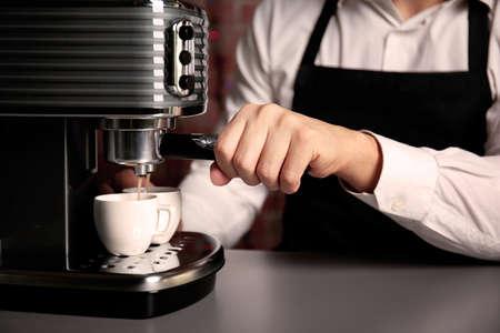 Male barista making fresh espresso in coffee maker, close up