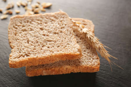 Sliced fresh bread with wheat spike on black table closeup Stock Photo