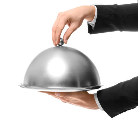 Hands of waiter holding metal tray with cover on white background