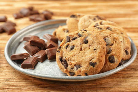 Tasty chocolate cookies on tray, wooden background,closeup