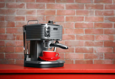 New electric coffee maker on brick wall background 版權商用圖片