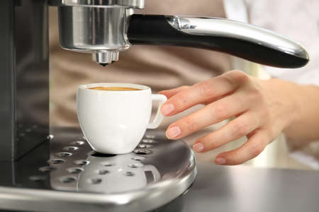 Woman making fresh espresso in coffee maker