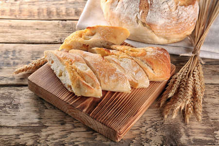 Sliced baguette bread on wooden cutting board closeup