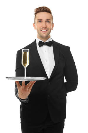 Handsome young waiter holding tray with glass of champagne, on white background