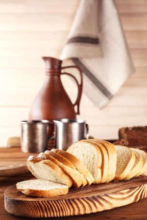 Sliced fresh bread on wooden cutting board closeup